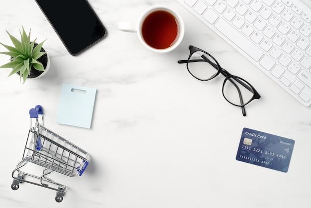 Vue de dessus du concept de magasinage en ligne avec carte de crédit, téléphone intelligent et ordinateur isolé sur fond de table blanche en marbre de bureau.