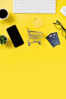 Vue de dessus du concept de magasinage en ligne avec carte de crédit, téléphone intelligent et ordinateur isolé sur fond de tableau jaune de bureau.