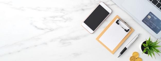 Vue de dessus du concept de plan financier avec carte de crédit, ordinateur portable, note sur la surface de la table de bureau blanc.