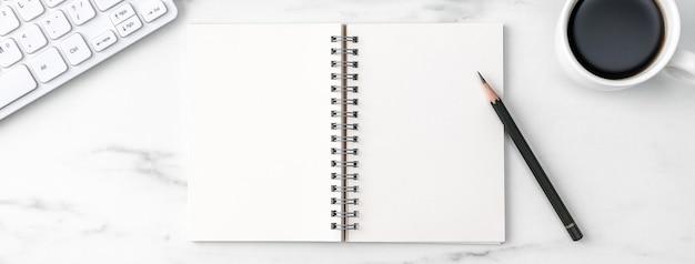 Vue de dessus du concept de travail confortable de table de bureau avec clavier, ordinateur portable, crayon, lunettes et café sur fond blanc en marbre clair.