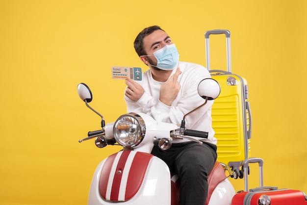Vue de dessus du concept de voyage avec un gars plein d'espoir en masque médical assis sur une moto avec une valise jaune dessus et tenant un billet
