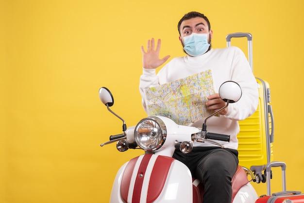 Vue de dessus du concept de voyage avec un gars surpris en masque médical assis sur une moto avec une valise jaune dessus et tenant une carte