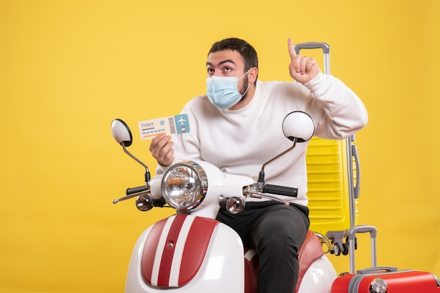 Vue de dessus du concept de voyage avec un jeune homme curieux en masque médical assis sur une moto