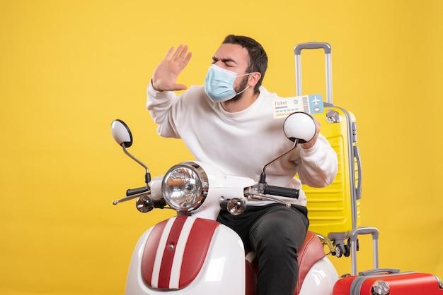 Vue de dessus du concept de voyage avec un jeune homme nerveux en masque médical assis sur une moto