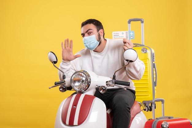 Vue de dessus du concept de voyage avec un jeune homme portant un masque médical assis sur une moto avec une valise jaune dessus et tenant un billet montrant cinq