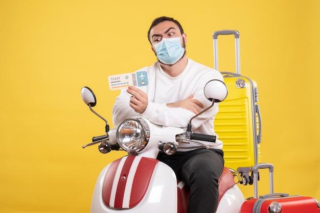 Vue de dessus du concept de voyage avec un jeune homme portant un masque médical assis sur une moto avec une valise jaune dessus et tenant un billet se sentant choqué