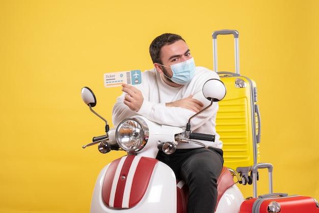 Vue de dessus du concept de voyage avec un jeune homme portant un masque médical assis sur une moto avec une valise jaune dessus et tenant un billet se sentant surpris