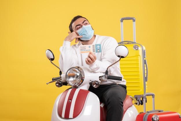 Vue de dessus du concept de voyage avec un jeune homme portant un masque médical assis sur une moto avec une valise jaune dessus et tenant un billet en train de m'appeler geste