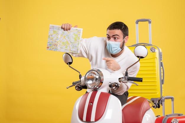 Vue de dessus du concept de voyage avec un jeune homme portant un masque médical debout près d'une moto avec une valise jaune dessus et tenant une carte pointant vers le haut