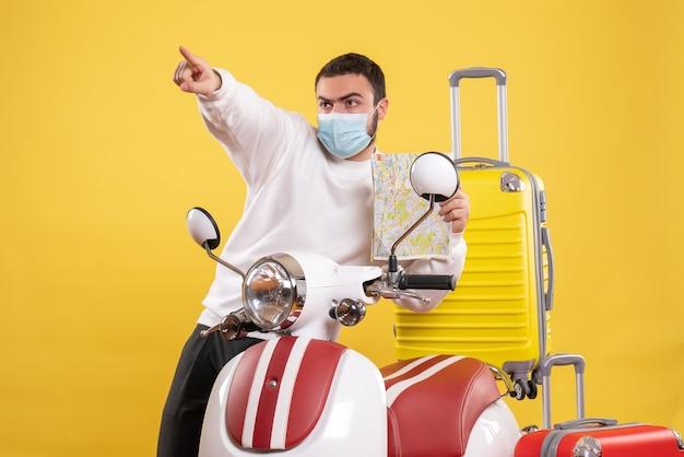 Vue de dessus du concept de voyage avec un jeune homme portant un masque médical debout près d'une moto avec une valise jaune
