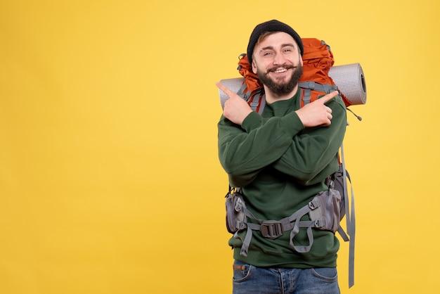 Vue de dessus du concept de voyage avec sourire heureux jeune homme avec packpack pointant vers le haut des deux côtés