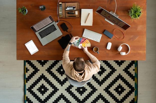 Vue de dessus du concepteur d'interface utilisateur occupé avec tatouage assis à table avec des appareils et regardant la palette de couleurs