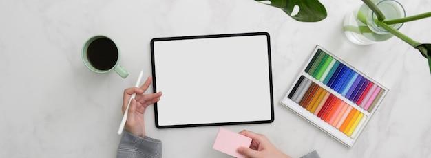 Vue de dessus du concepteur travaillant avec une maquette de tablette, des fournitures de concepteur et un pense-bête
