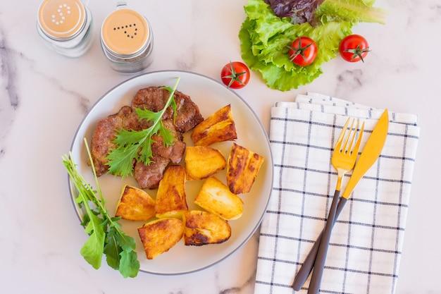 Vue de dessus du cou de porc grillé servi avec pommes de terre frites, tomates et cetcup sur fond clair.