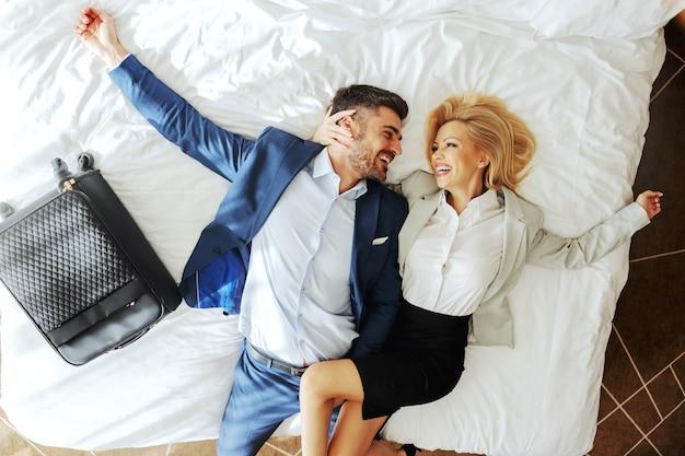 Vue de dessus du couple d'âge moyen habillé formel couché sur le lit et étreignant. ils vont passer un merveilleux week-end.