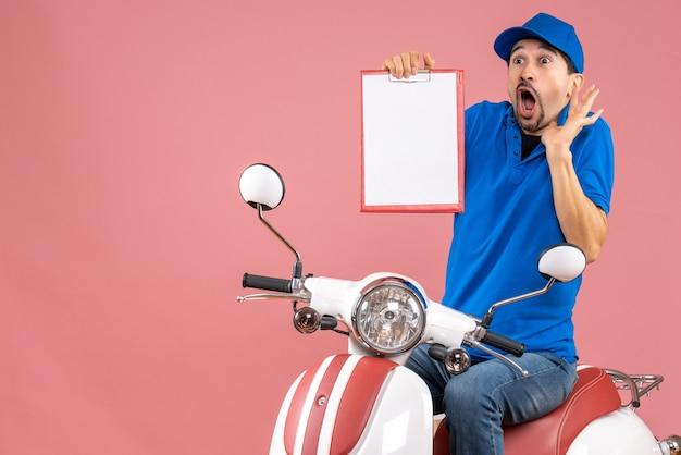 Vue de dessus du courrier effrayé homme portant un chapeau assis sur un scooter tenant un document sur fond de pêche pastel