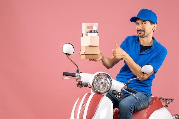 Vue de dessus du courrier homme portant un chapeau assis sur un scooter montrant des commandes faisant un geste ok sur fond de pêche pastel