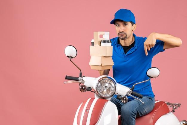 Vue de dessus du courrier homme portant un chapeau assis sur un scooter montrant des commandes pointant vers le bas sur fond de pêche pastel