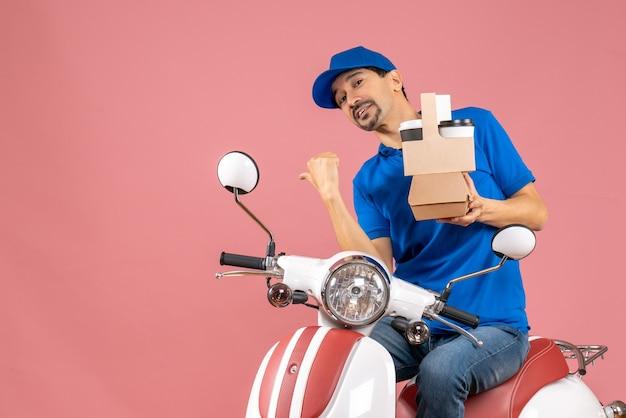 Vue de dessus du courrier homme portant un chapeau assis sur un scooter tenant des commandes pointant vers l'arrière sur fond de pêche pastel