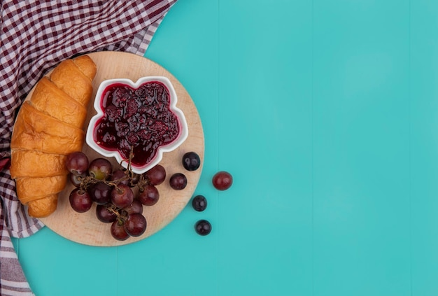 Vue de dessus du croissant et de la confiture de framboises dans un bol de raisin sur une planche à découper sur un tissu à carreaux sur fond bleu avec copie espace