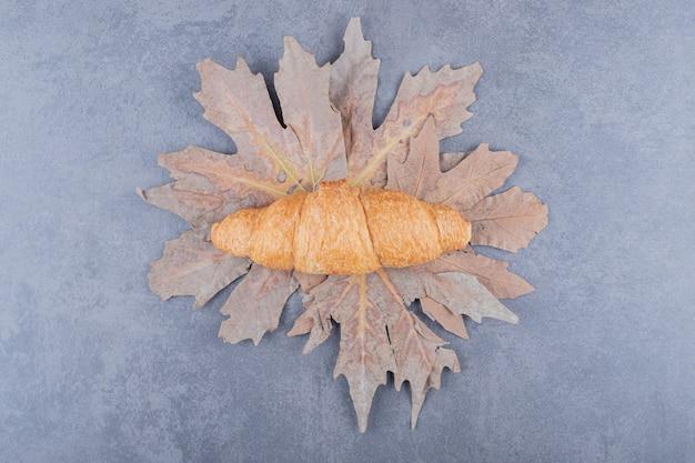Vue de dessus du croissant français classique sur feuilles sèches