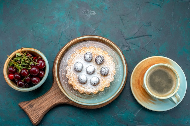 Vue de dessus du cupcake avec cerises rondes et sucre en poudre à côté de la plaque de cerises et latte