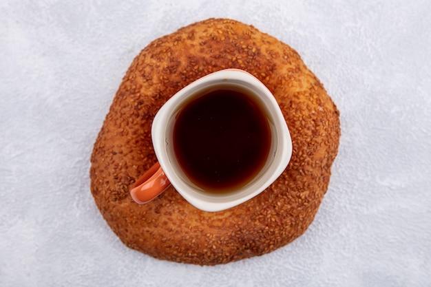 Vue de dessus du délicieux bagel turc au sésame avec une tasse de thé sur fond blanc