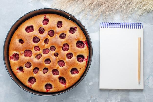 Vue de dessus du délicieux gâteau aux fraises cuit au four avec des fraises rouges fraîches à l'intérieur avec casserole et bloc-notes sur blanc, gâteau biscuit aux fruits