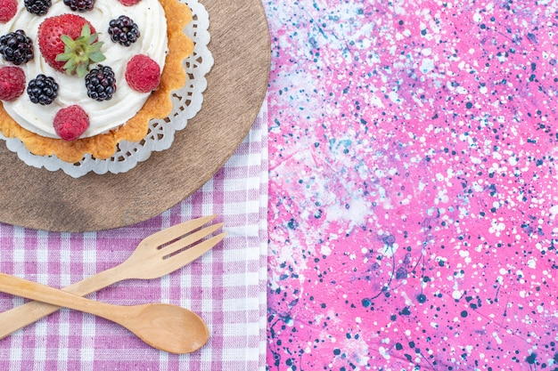 Vue de dessus du délicieux gâteau à la crème et aux baies fraîches sur la lumière, biscuit gâteau aux petits fruits