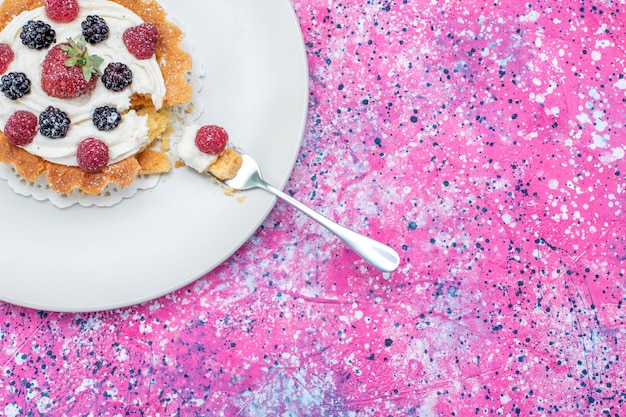 Vue de dessus du délicieux gâteau crémeux avec différentes baies fraîches à l'intérieur de la plaque blanche sur un bureau lumineux, berry fruit frais aigre