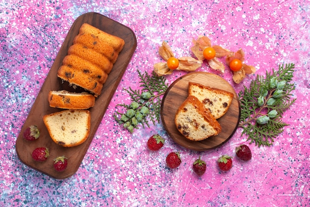 Vue de dessus du délicieux gâteau sucré et délicieux tranché avec des fraises rouges fraîches sur la surface rose