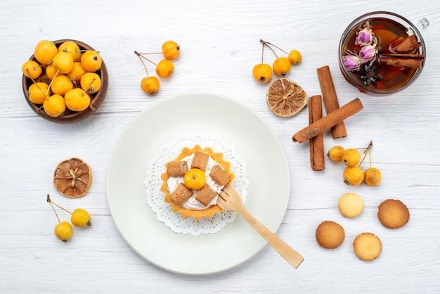 Vue de dessus du délicieux petit gâteau avec des cerises jaunes, des coookies à la cannelle et du thé sur la lumière, biscuit gâteau biscuit sucré