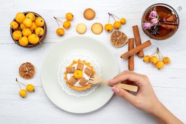 Vue de dessus du délicieux petit gâteau se faire manger par une femme avec des cerises jaunes, des coookies à la cannelle et du thé sur un bureau léger, biscuit gâteau biscuit sucré