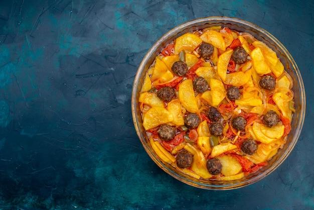 Vue de dessus du délicieux repas de pommes de terre avec des boulettes de viande et des tomates sur la surface bleu foncé