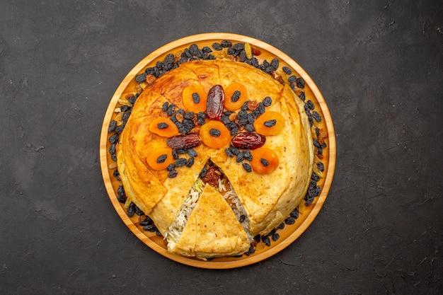 Vue de dessus du délicieux repas de riz shakh plov cuit à l'intérieur d'une pâte ronde avec des raisins secs sur une surface gris foncé