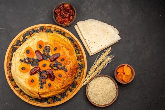 Vue de dessus du délicieux repas de riz shakh plov cuit à l'intérieur d'une pâte ronde avec des raisins secs sur la surface grise