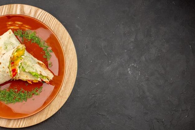 Vue de dessus du délicieux sandwich à la viande shaurma en tranches à l'intérieur de la plaque sur le noir