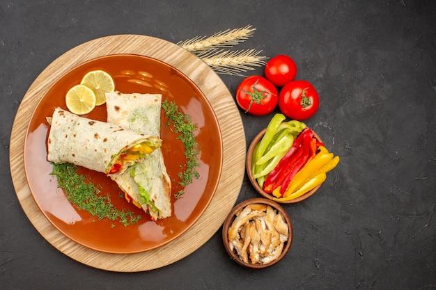 Vue de dessus du délicieux sandwich à la viande shaurma en tranches avec des légumes sur fond noir