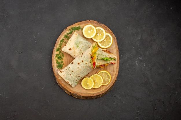 Vue de dessus du délicieux sandwich à la viande shaurma en tranches avec des tranches de citron sur fond noir