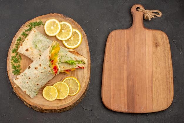 Vue de dessus du délicieux sandwich à la viande shaurma en tranches avec des tranches de citron sur gris noir