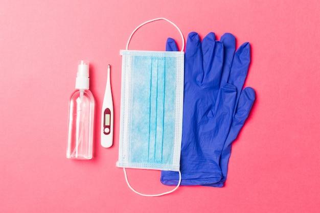 Vue de dessus du désinfectant pour les mains à l'alcool, des gants en latex, un thermomètre numérique et un masque médical sur fond rose. concept d'équipement de protection contre les virus avec espace copie