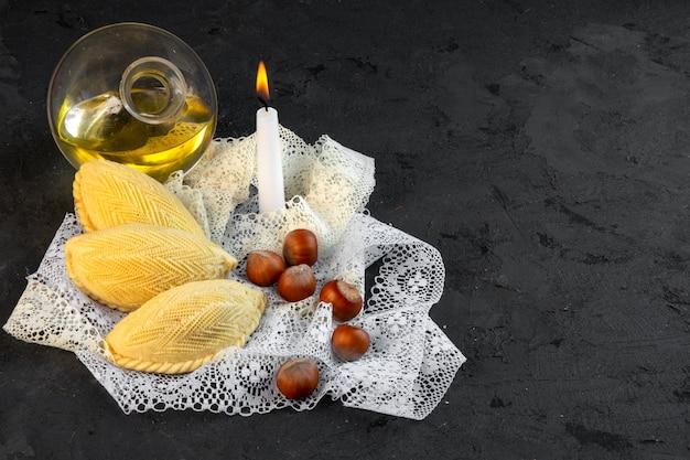 Vue de dessus du dessert national d'azerbaïdjan shekerbura et une bouteille d'huile d'olive et bougie sur dentelle sur fond noir