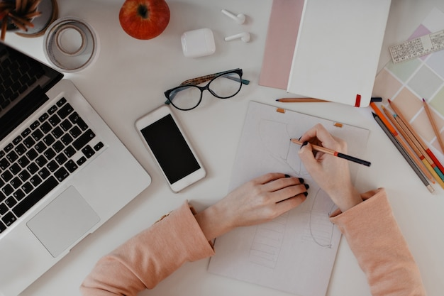 Vue de dessus du dessin des mains. portrait d'outils de bureau, crayons, écouteurs, ordinateur portable et smartphone sur blanc.