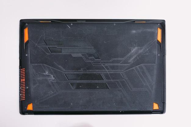Vue de dessus du dessous d'un ordinateur portable avant d'être réparé sur une table blanche