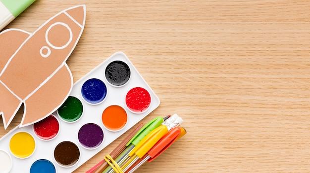 Vue de dessus du dos aux fournitures scolaires avec aquarelle et crayons