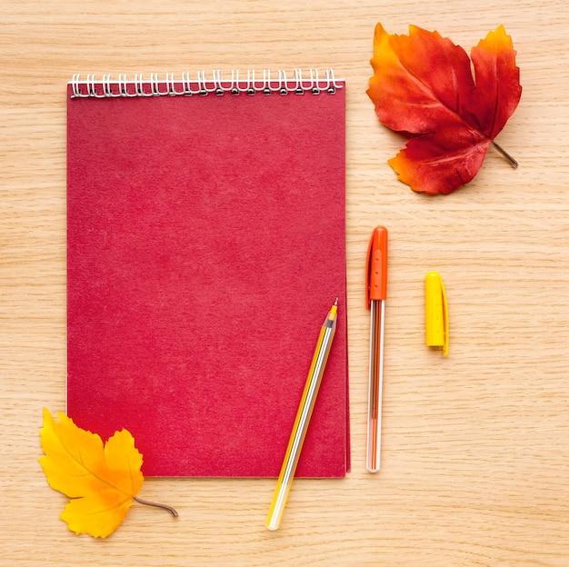 Vue de dessus du dos aux fournitures scolaires avec des feuilles et un cahier