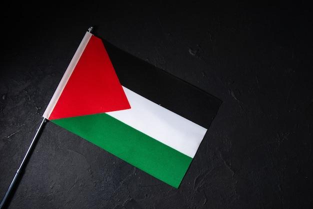 Vue de dessus du drapeau de la palestine sur un mur sombre