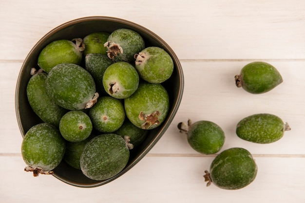 Vue de dessus du feijoa vert frais sur un bol sur une surface en bois blanche
