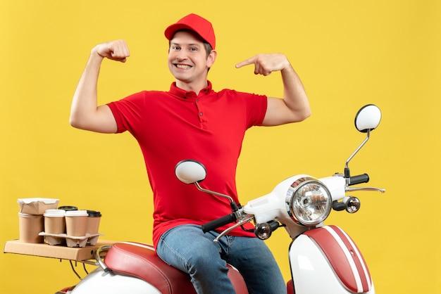 Vue de dessus du fier jeune homme portant un chemisier rouge et un chapeau livrant des commandes sur fond jaune