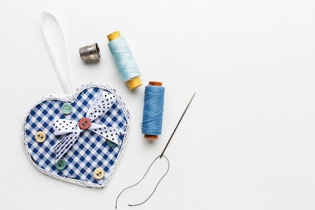 Vue de dessus du fil avec des aiguilles et du tissu en forme de coeur